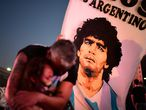 TOPSHOT - A father and her daughter, fans of Argentinian football legend Diego Maradona, mourn as they gather by the Obelisk to pay homage on the day of his death in Buenos Aires, on November 25, 2020. - The body of Argentine football legend Diego Maradona, who died earlier today, will lie in state at the presidential palace in Buenos Aires during three days of national mourning, the presidency announced. (Photo by RONALDO SCHEMIDT / AFP)