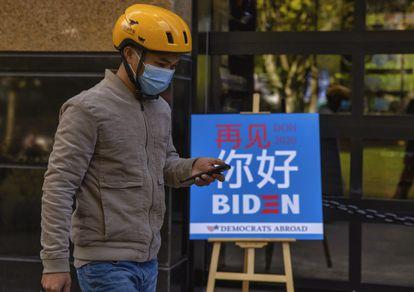 Entregador passa em frente a um bar de Xangai que exibiu a apuração das eleições norte-americanas.