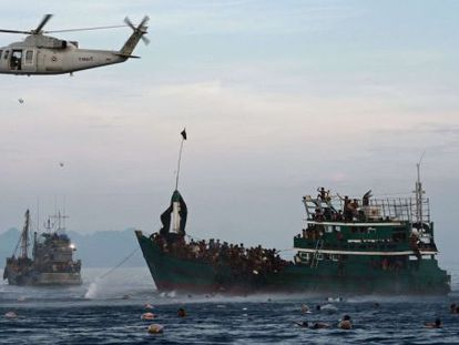 Imigrantes se atiram à água para pegar alimentos distribuídos por militares tailandeses.