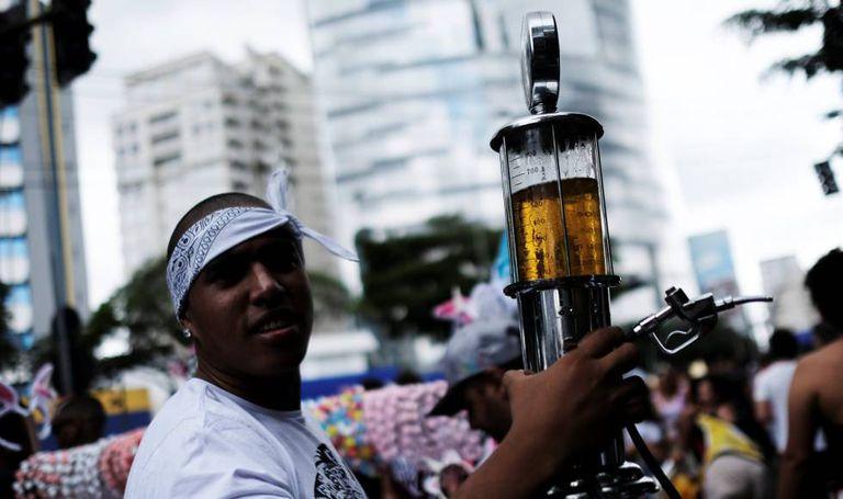 Folião leva cerveja em uma mini bomba de gasolina, sábado em São Paulo.