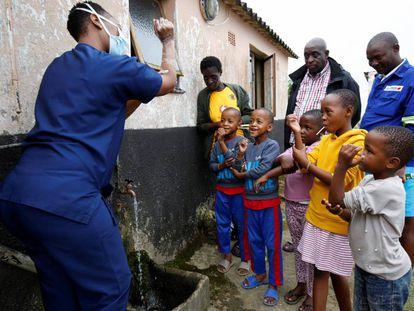 Profissional sanitária no subúrbio de Umlazi, perto de Durban (África do Sul), ensina crianças a lavarem as mãos para deterem o contágio do coronavírus, em 4 de abril.