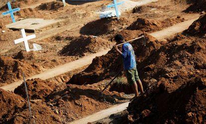 Funcionário da prefeitura prepara covas para enterrar as vítimas do massacre.