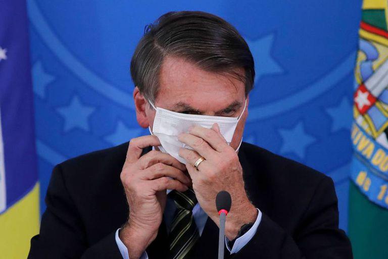 O presidente Jair Bolsonaro, colocando uma máscara de proteção durante um evento no Palácio do Planalto, em 18 de março. Aprovação do Governo se mantém estável.