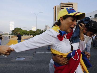 Uma opositora ao regime de Maduro depois do lançamento de gás lacrimogêneo, nesta terça-feira em Caracas.