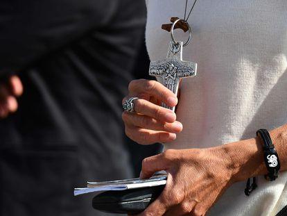 Mulher segura crucifixo durante a oração do Angelus conduzida pelo papa Francisco em 25 de outubro na praça de São Pedro (Vaticano).