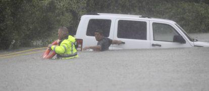 Homem é resgatado de seu carro em Houston, no domingo.