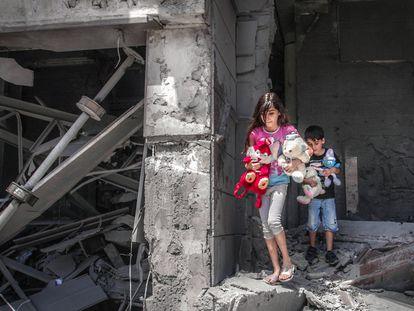 Crianças palestinas resgatam brinquedos na casa onde viviam, que ficou gravemente destruída pelos ataques aéreos israelenses em Gaza no dia 17 de maio de 2021.