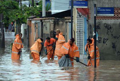 Garis tentam limpar bueiros de área inundada do Rio de Janeiro.