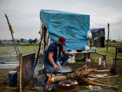 Sem-teto cozinha sob a intempérie, em Buenos Aires, em agosto de 2020.