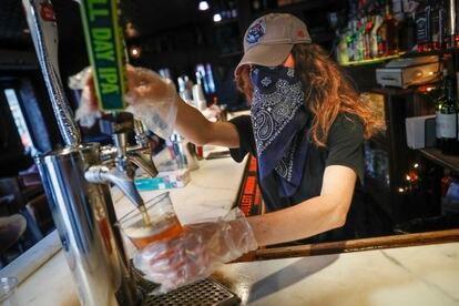 Garçonete serve uma cerveja em um bar de Nova York, em junho.