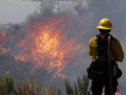 Bombeiro monitora o avanço do fogo em Santa Clarita, Califórnia.