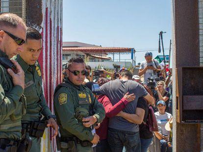 Uma família se abraça na cerca de Tijuana, vigiada pela polícia de fronteiras.