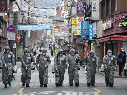 Soldados sul-coreanos desinfetam uma rua de Seul.