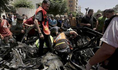 Palestinos inspecionam os restos do veículo do dirigente do Hamas Mohamed Ghoul, atingido neste domingo em um ataque contra Gaza.