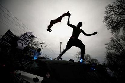 Manifestante pula em cima de uma viatura da polícia durante os protestos em Minneapolis, no último domingo.