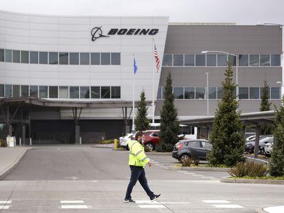 Funcionário passa diante da fábrica da Boeing em Everett (Washington, EUA), na terça-feira passada.