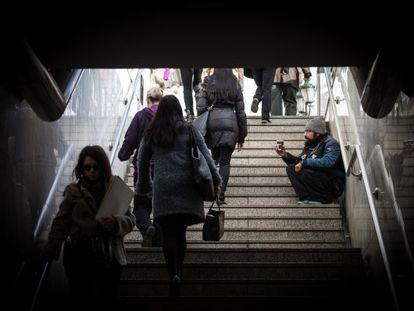 Homem pede esmolas na saída de estação de metrô em Atenas.