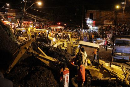 Duas retroescavadeiras retiram os escombros em uma favela de Niterói.