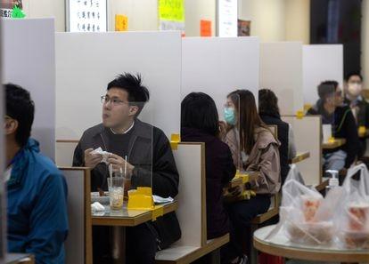 Em um restaurante em Hong Kong as mesas são divididas com uma tela de plástico.