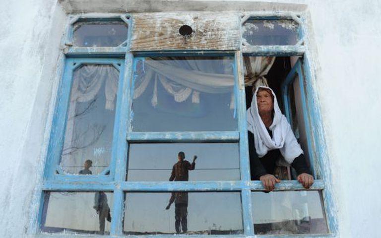 A viúva afegã Bibikoh na janela de sua casa.
