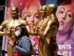 Nikki Slaughter of Tampa Bay, Fla., poses for a photo near fake Oscar statues on Hollywood Blvd., Thursday, April 15, 2021, in Los Angeles. The 93rd Academy Awards will be held in various locations including the Dolby Theatre in Hollywood on Sunday, April 25. (AP Photo/Chris Pizzello)