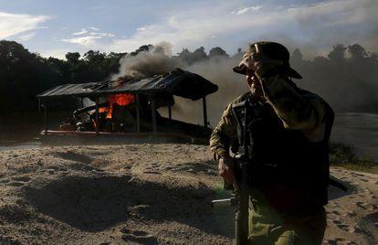 Agente do Ibama em um garimpo ilegal queimado nas margens do rio Uraricoera, em Roraima.