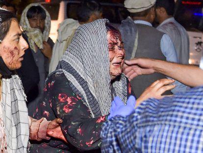Uma mulher ferida chega ao hospital depois das duas explosões desta quinta-feira perto do aeroporto da capital afegã.