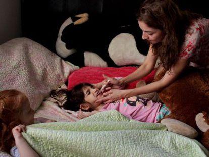 A mãe de Graciela Elizalde dá o remédio a sua filha.
