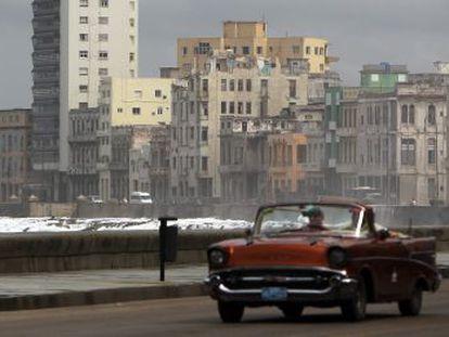 Um carro velho circula por Havana.