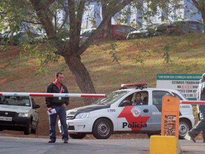 Policial e funcionários na frente da fábrica assaltada, em Campinas.