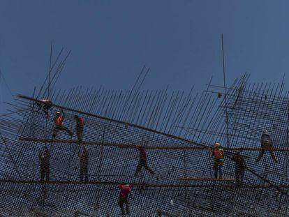 Operários do setor de construção trabalham em uma ponte rodoviária.