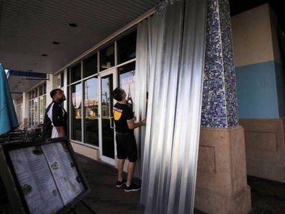 Empregados de um restaurante cobrem portas e janelas em Coral Springs (Flórida), nesta quarta-feira.