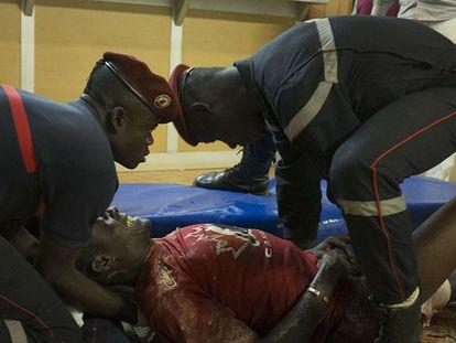 Um ferido é atendido por policiais franceses nas imediações do Hotel Splendid.