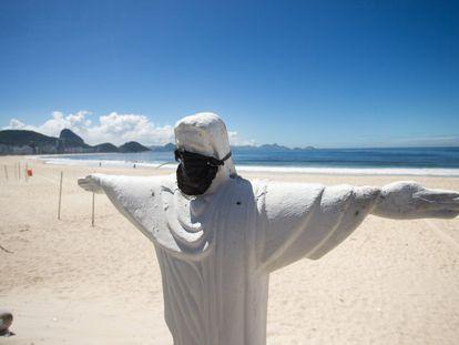 Um Cristo com máscara numa Copacabana praticamente vazia, na sexta-feira.