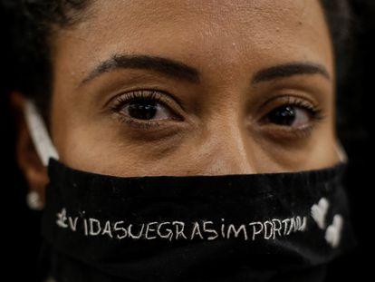 """Uma mulher protesta contra o assassinato de João Alberto Silveira Freitas em um Carrefour da Barra da Tijuca, no Rio de Janeiro. Em sua máscara, lê-se: """"Vidas negras importam""""."""
