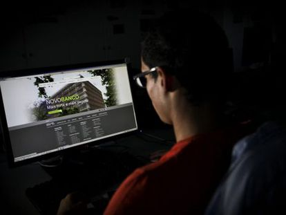 Um homem observa uma tela de computador.