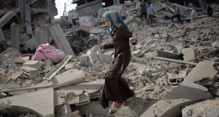 Mulher caminha entre os escombros de Gaza, em julho de 2014.