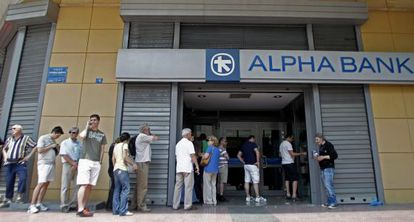 Pessoas fazem fila para sacar dinheiro em caixas eletrônicos em Atenas.