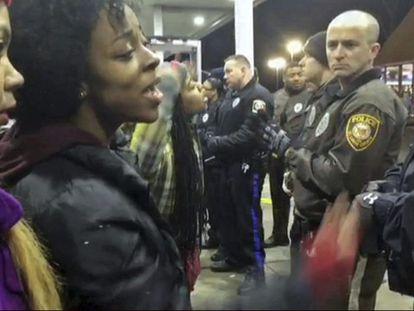 Várias pessoas discutem com policiais.