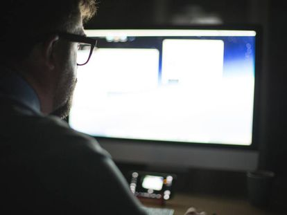 Um homem utiliza um computador.