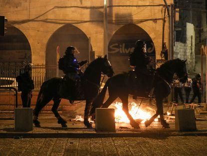 Policiais israelenses a cavalo patrulham os arredores da porta de Damasco, em Jerusalém, durante os distúrbios da noite de quinta-feira.