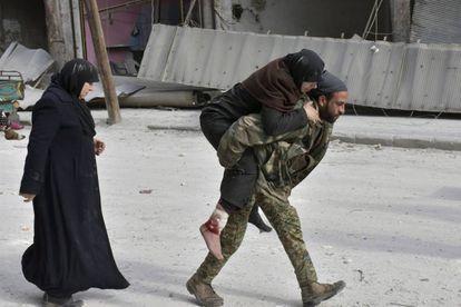 Soldado sírio socorre uma mulher ferida em Aleppo, após o Exército tomar o controle sobre a região. Milhares de civis aguardam para sair da cidade, devastada pela guerra que já dura cinco anos.