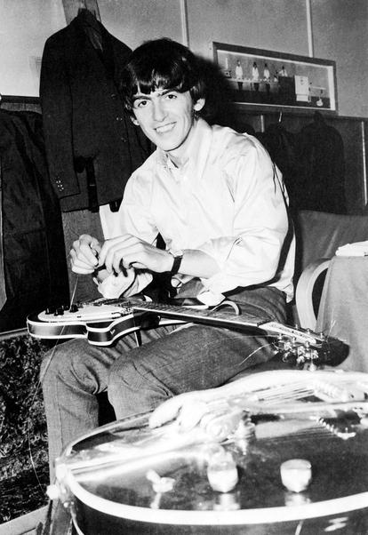 O músico troca as cordas da sua guitarra em 1965, na época dos Beatles.