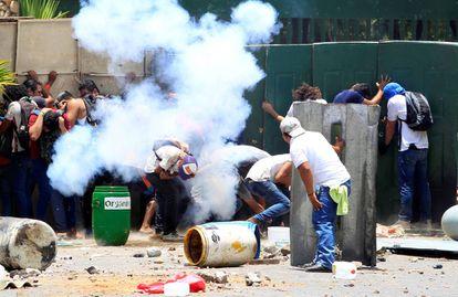 Manifestantes se protegem durante os protestos na Universidade Agrária de Manágua.