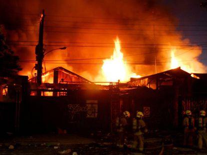 Bombeiros combatem incêndio em um armazém durante os distúrbios no Chile.