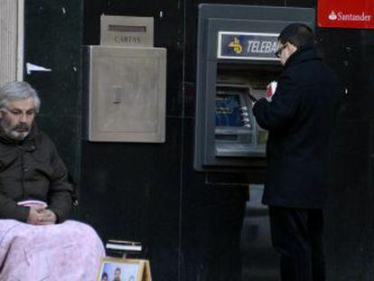 Um homem pede esmolas na porta de um caixa automático em Madri.