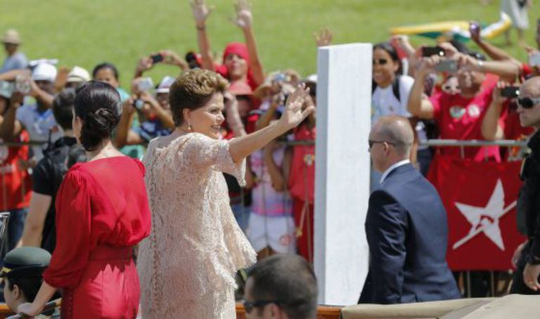Dilma acena para militantes ao lado da filha.
