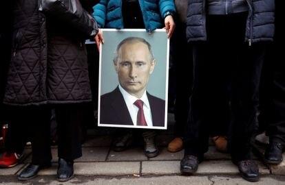 Um seguidor do presidente russo Vladimir Putin mostra um cartaz com sua imagem em Belgrado, na Sérvia, em 2019.