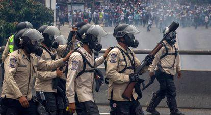 Agentes da Guarda Nacional Bolivariana bloqueiam a passagem de manifestantes em abril.