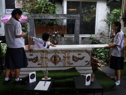 Uma jovem sai do caixão instalado como parte da decoração no Kid Mai Cafe de Bangcoc.